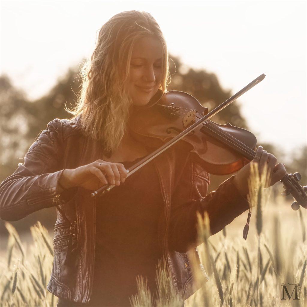 Nine Gees steht im Feld und spielt Geige
